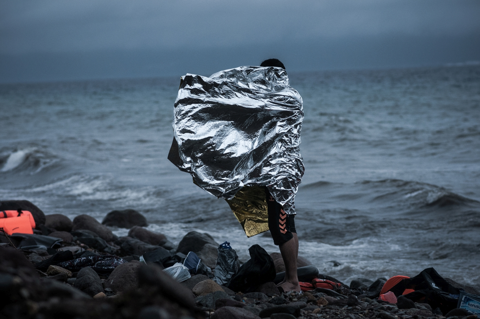 A man stands on the shore as refugees and migrants arrive on the Greek Lesbos island after crossing the Aegean Sea from Turkey, October 2015.